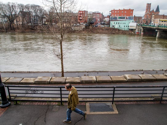 A man walks near the banks of the Chenango River in