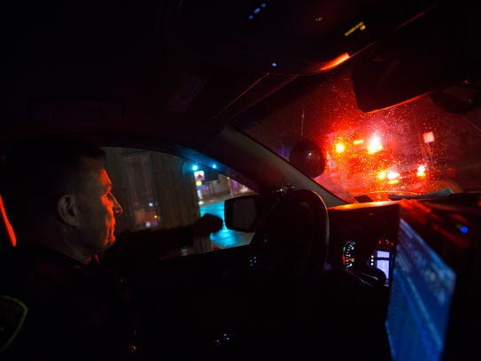 Deputy Will Andres watches as an ambulance passes on