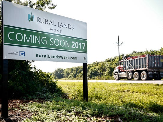 A truck passes by a sign for a proposed housing development