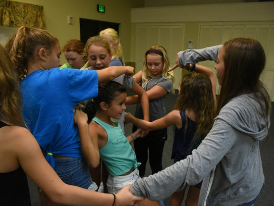 The cast performs an exercise in which they clasp hands,