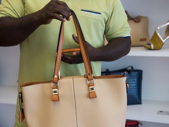 Jon Kane, a handbag designer, holds a handbag in his