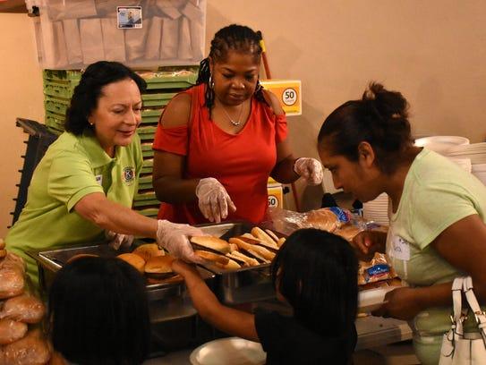 Volunteers Susan Van Kleef and Paulette Thomas hand