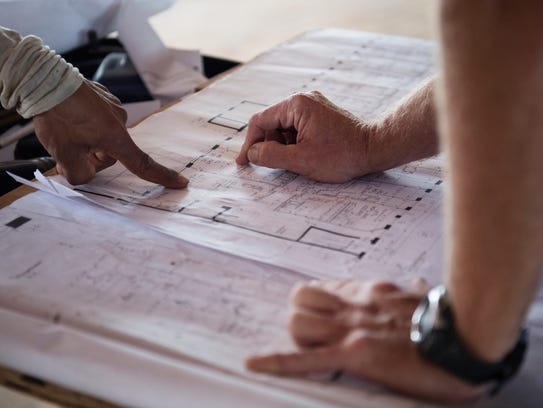 Triangle Construction workers look at plans as they