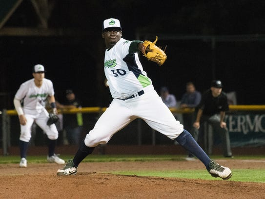 Vermont relief pitcher Wandisson Charles (30) delivers