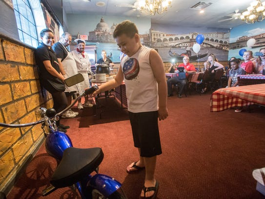 """Cohen Powell looks at his new bicycle donated by """"Make"""