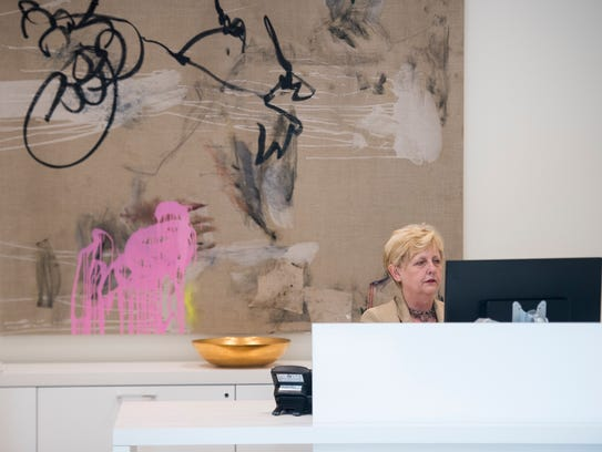 Sandra Brockman of the Hughes Agency works at her desk at the company's new building, 110 E. Court St., in downtown Greenville on Tuesday, Oct. 10, 2017.