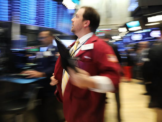 High-flying Dow: Traders work on the floor of the New
