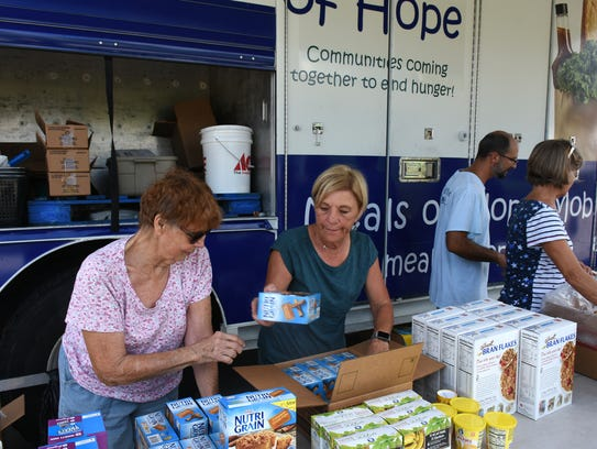 Volunteers organize supplies from the truck at Lely
