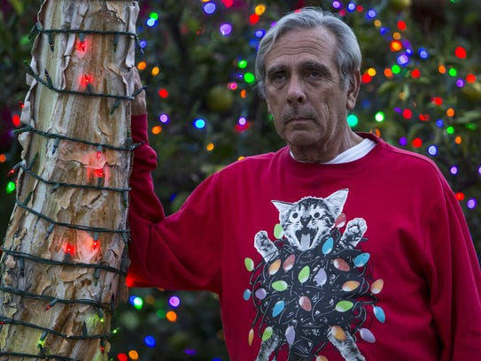 Lee Sepanek stands in front of Christmas lights he helped set up in his neighbor's yard.