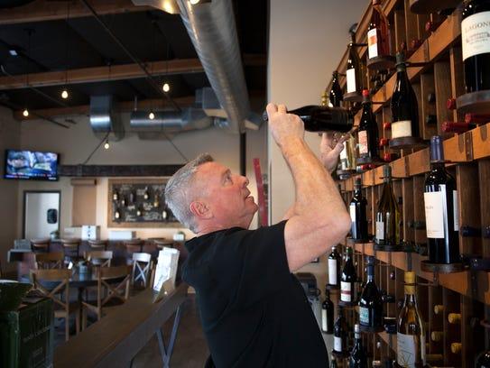 Owner Patrick Mervyn stocks a wine rack at RELM Wine