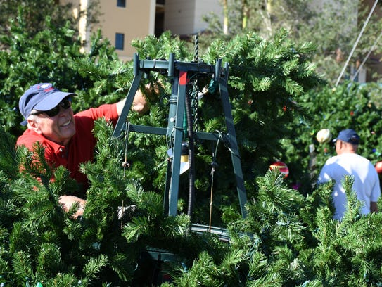 Gene Burson puts together the tree's top section. Workers