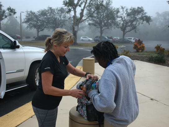 Allyson Richards helps a young girl pick up food from