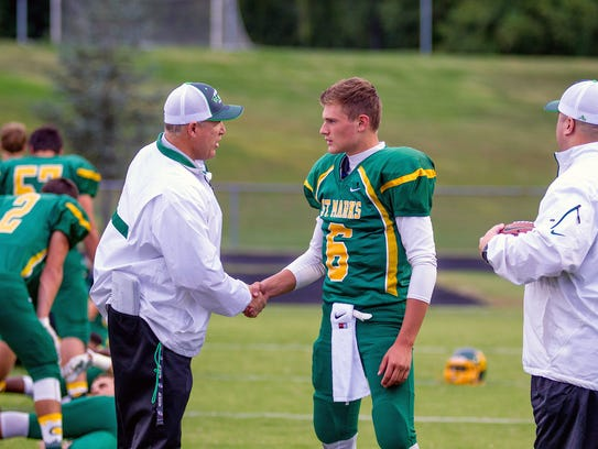 Coach John Wilson shakes hands with player Billy Sullivan.