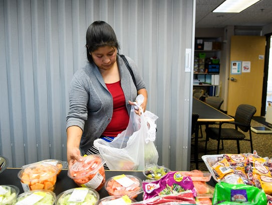 Cecilia Morales picks out produce at the free farmer's
