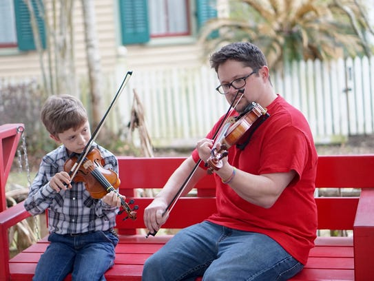 Owen Meche, left, receives fiddle tips from music teacher Brazos Huval.