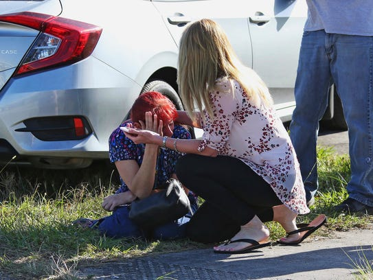 A woman consoles another as parents wait for news regarding