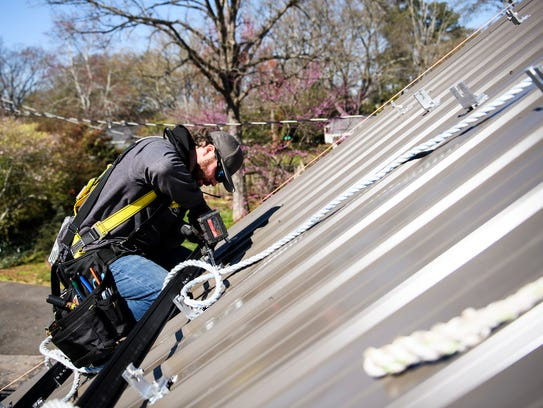 Nick Messer of Summit Solar begins to install solar panels on a home on Thursday, March 15, 2018.