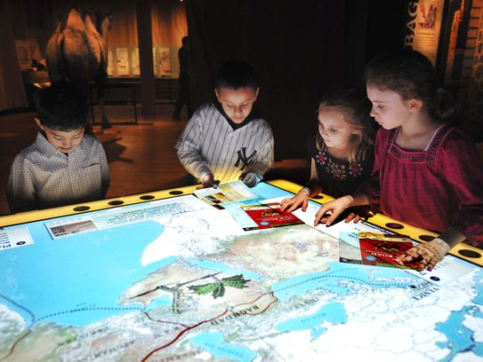 Visitors to COSI explore an interactive map of the