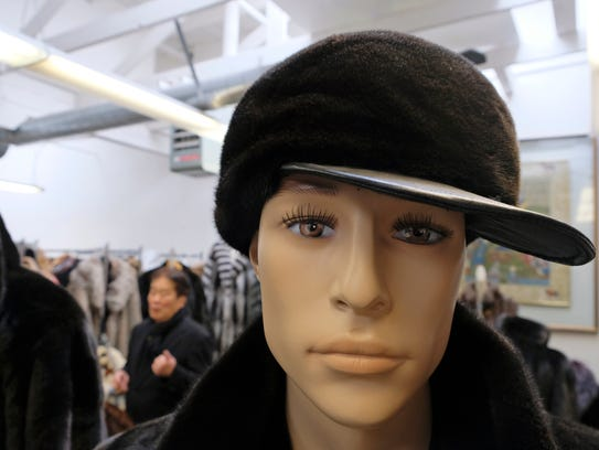 A hat sits on a mannequin as Benjamin Lin talks about