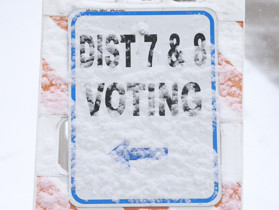"""A """"district 7 & 8 voting"""" sign covers with Tuesday"""