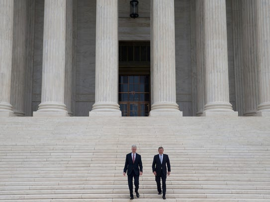 Justice Neil Gorsuch descends the steps of the Supreme