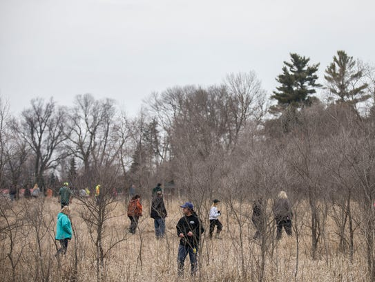 A team of volunteers searches a wooded area several