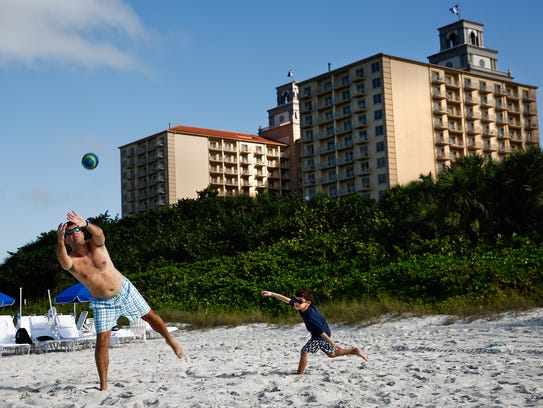 Jonathan Feit leans in to catch a football from his wife Beth while being chased by their son Joshua, 5, on Vanderbilt Beach in front of the Ritz-Carlton, Naples on Wednesday, Dec. 30, 2015.