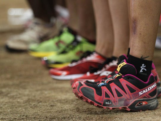 A runner flexes her feet to warm up at the starting