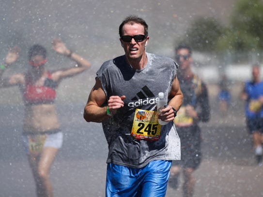 Participants run through water sprayed by a Scottsdale