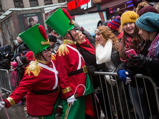 Revelers take photos with crowd members during the