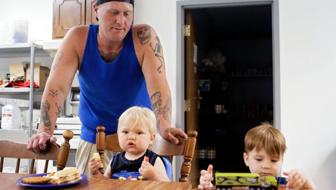 Travis Scullen watches his sons eat and play inside the kitchen at Hancock Hope House in Greenfield, Ind., on Wednesday, Aug.16, 2017. Scullen and his family ended up at the homeless shelter after the house he was renovating was condemned.