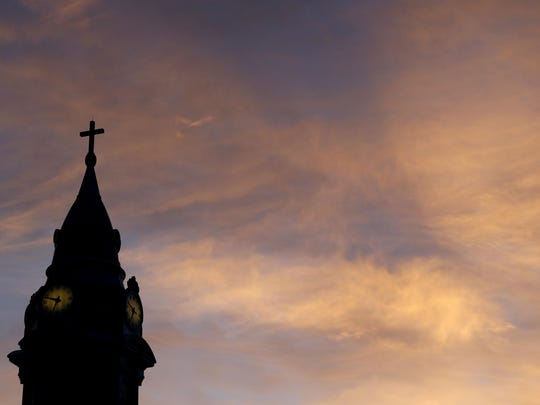 FILE - In this Sept. 27, 2015 file photo, clouds are lit by the rising sun over St. Augustine Roman Catholic Church in Philadelphia. Pennsylvania's Roman Catholic dioceses have paid nearly $84 million to 564 victims of sexual abuse, a tally that's sure to grow substantially in 2020 as compensation fund administrators work through a backlog of claims, according to an Associated Press review. (AP Photo/Julio Cortez)