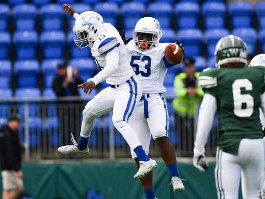 Community School's Israel Anis (right) and Jason Beauplan celebrate after Anis recovered a fumbled snap in the American Football Showcase on Friday, ,Sept. 2, 2016, in Dublin, Ireland.