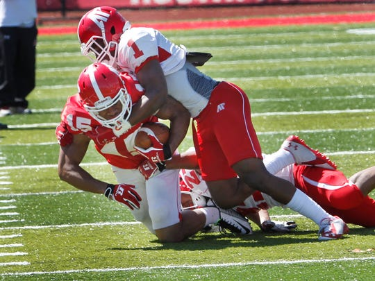 Running back Wesley Thomas is stopped by Roderick Owens during the annual Red and White game at Governors Stadium Saturday..