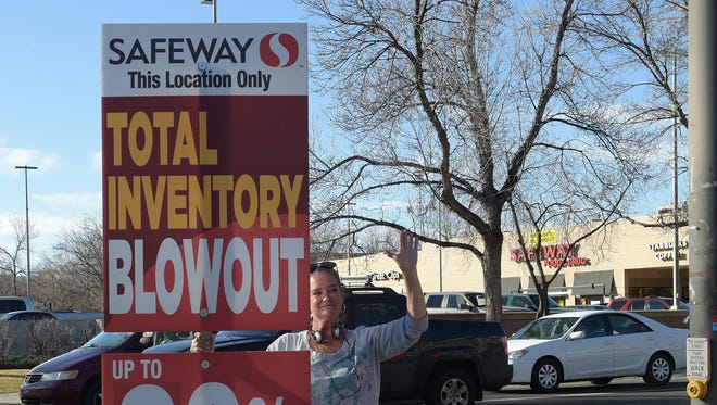 JoAnn Beidler holds a sign advertising Safeway's going-out-of-business sale on on Feb. 15