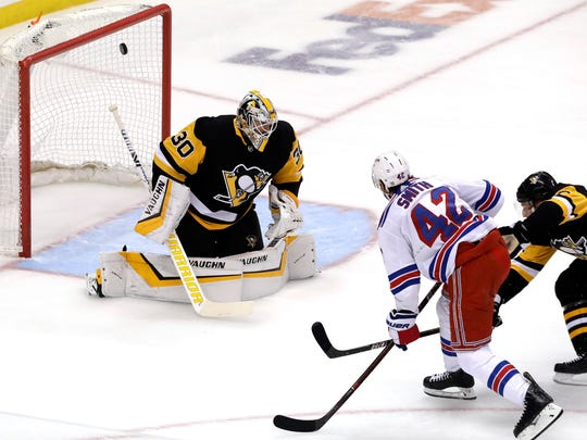 New York Rangers' Brendan Smith (42) scores against Pittsburgh Penguins goaltender Matt Murray (30) with Penguins' Jack Johnson, right, defending during the first period of an NHL hockey game in Pittsburgh, Saturday, April 6, 2019. (AP Photo/Gene J. Puskar)