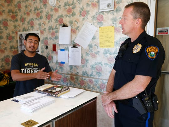 Darold Donathan, of the Branson Police Department, talks with Santos Hulsizer, co-owner of the Good Shepherd Inn, on Tuesday, Oct. 11, 2016. A new city ordinance will put a tier system in place for the hotels and motels in the area.