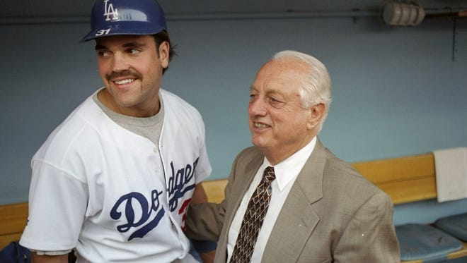 Former manager Tommy Lasorda and catcher Mike Piazza of the Los Angeles Dodgers pose together Aug. 15, 1997, for a picture during the retiring of Lasorda's number before a game against the Cincinnati Reds at Dodger Stadium.