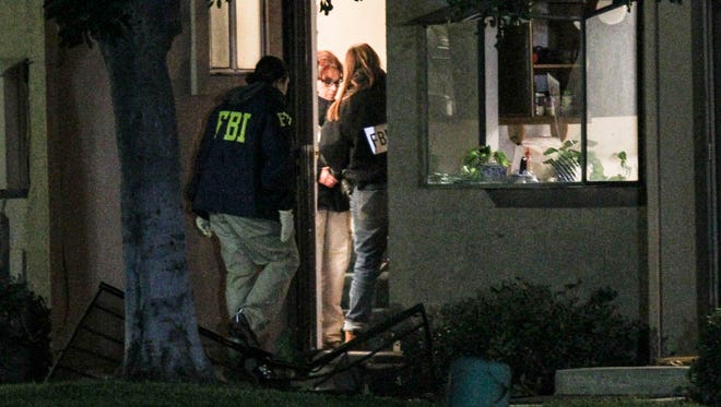 FBI agents search outside a home in connection to the shootings in San Bernardino on Thursday in Redlands, Calif. A heavily armed man and woman opened fire Wednesday on a holiday banquet, killing multiple people and seriously wounding others in a precision assault, authorities said. Hours later, they died in a shootout with police.