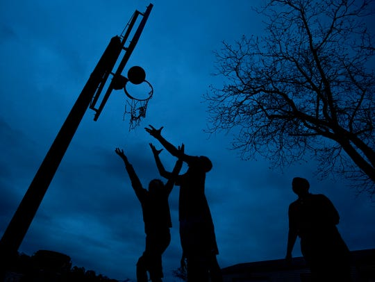 Children play basketball as the sun sets at That's