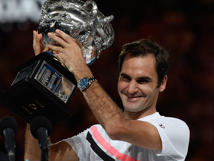 Roger Federer holds the Australian Open trophy, celebrating