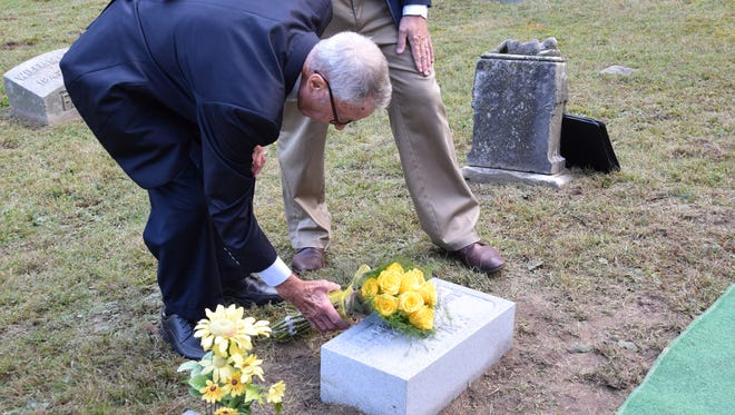 Dick Leill places 10 yellow roses on the grave of Ray Ewry on Friday, Sept. 29, at Spring Vale Cemetery in Lafayette. Ewry, a Lafayette native and Purdue graduate, won 10 gold medals during the Olympics between 1900 and 1908. This week, Leill  replaced Ewry's headstone to correct mistakes.