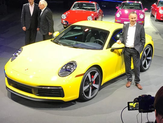 A Porsche designer poses with the new 911