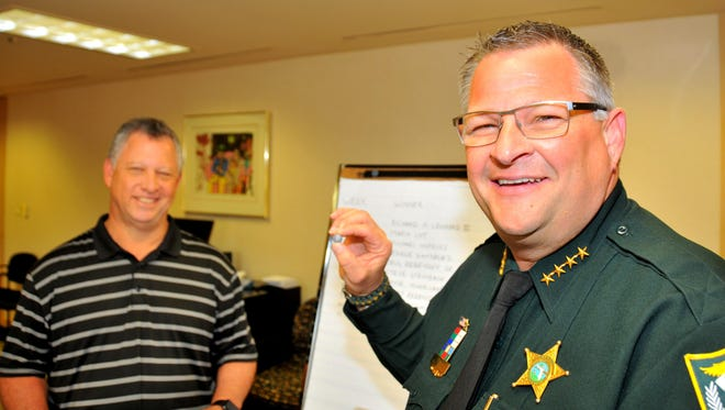 Brevard County Sheriff Wayne Ivey, winner of FLORIDA TODAY's Celebrity Picks football contest, came to the FLORIDA TODAY office to pick the winner of a 60-inch TV. Robert Rebensky, lucky No. 8, was the number that Sheriff Ivey chose. In background is FLORIDA TODAY president and pubisher Jeff Kiel.