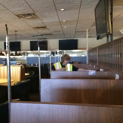 A PuroClean employee wipes down booths in Kroll's West