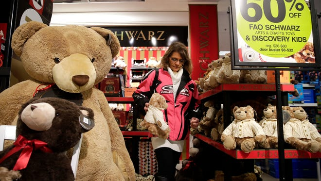 Christine Voigt, of Appleton, stops to pick up a stuffed animal during her Thanksgiving Day shopping at Younkers Thursday, in Grand Chute. Voigt was the first person in line before the store opened.