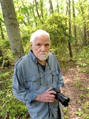 Bates Littlehales poses for a portrait in a wooded