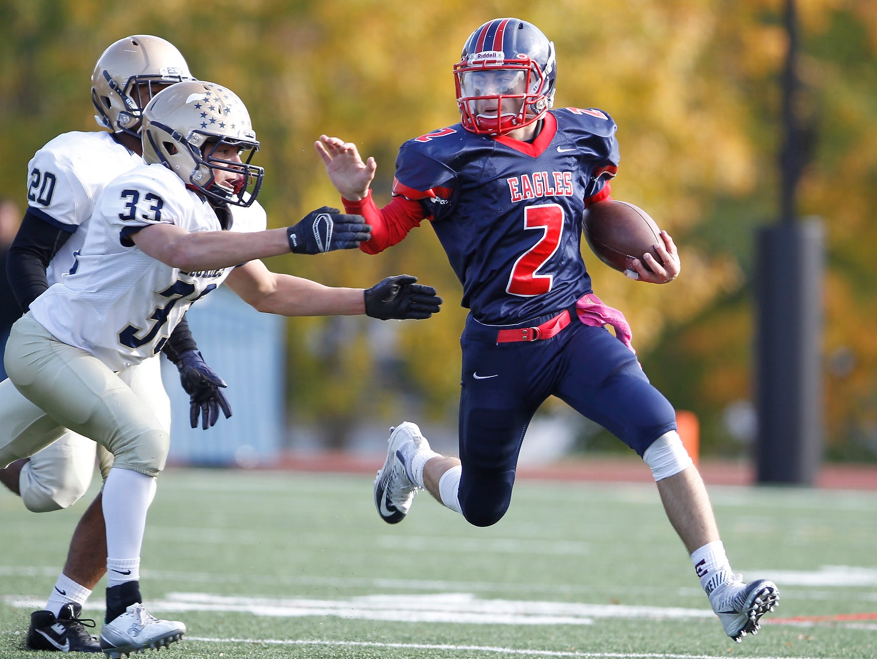Eastchester quarterback John Arcidiacono (2) fends off Lourdes' line backer Joe Scallion (33) during their 19-27 loss to Our Lady of Lourdes High School in the class A semi-final football game in Eastchester on Saturday, Oct. 31, 2015.