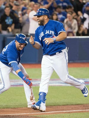Toronto Blue Jays first baseman Kendrys Morales celebrates with Toronto Blue Jays shortstop Troy Tulowitzki after hitting a walk off home run in the ninth inning during a game against the Baltimore Orioles at Rogers Centre. The Toronto Blue Jays won 2-1.