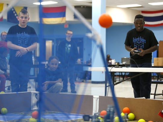 Jabari Acre, right, operates his Rickards' team robot while teammate Justin Huber watches as they compete for team R³ at the robotics competition.